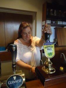 Nina, barmaid and secretary, pulling a pint at the Old Forge
