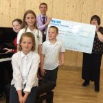 Fen Edge Community Association present a cheque to Cottenham Primary School towards a new piano
